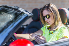 Young woman driving a cabriolet car distracted with her phone an Royalty Free Stock Image