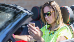 Young woman driving a cabriolet car distracted with her phone an Stock Photography