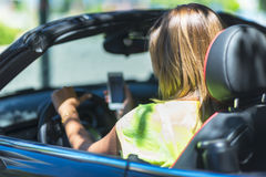 Young woman driving a cabriolet car distracted with her phone an Royalty Free Stock Photography