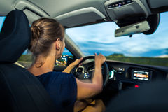 Young, woman driving a car at dusk Stock Photo