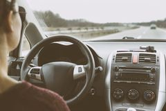 Young woman driving car on highway. Driver`s perspective holding steering wheel Stock Photos