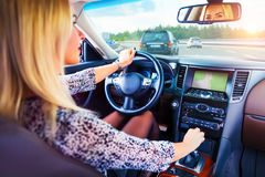 Young woman driving a car on a highway. Young business woman driver driving a car on a highway Royalty Free Stock Image