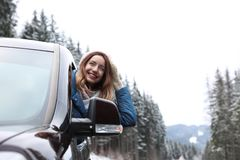 Young woman driving car and looking out of window on road. Winter vacation stock photo