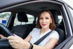 Young woman driving car on the road. Young woman in white shirt driving car on the road. Hispanic girl steering wheel in auto Royalty Free Stock Image