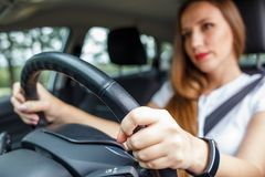 Young woman driving car on the road. Young woman in white shirt driving car on the road. Hispanic girl steering wheel in auto Stock Photo