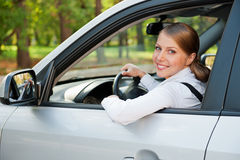 Young woman driving the car and smiling Stock Photos