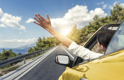 A young woman is driving by car to the sea and waving her hand from a yellow convertible car. Vacation on the sea coast. Stock Image