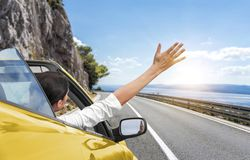 A young woman is driving by car to the sea and waving her hand from a yellow convertible car. Vacation on the sea coast. Stock Images