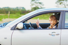 Young woman driving a car and using phone Royalty Free Stock Photos