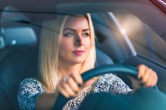 Young woman driving a car. Young thoughtful confident woman driving a modern luxury car royalty free stock photo