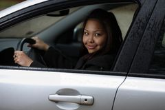Young woman driving her new car. Pretty young asien woman driving her new car Stock Photography
