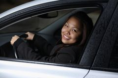 Young woman driving her new car. Young woman smiling as she sits comfortably in her brand new car Stock Photo