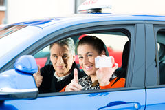 Young woman at driving lesson Stock Images