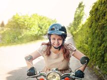 Young woman driving a scooter on a countryside road stock photo