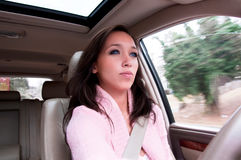 Young Woman Driving a Vehicle. Concentrating young woman dressed in pink driving a car; blur in the background portrays that the vehicle is in motion royalty free stock images
