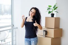 Young woman dropping cardboard box. Moving into new home.  Royalty Free Stock Image