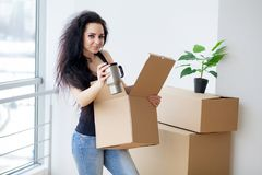 Young woman dropping cardboard box. Moving into new home.  Stock Photo