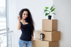 Young woman dropping cardboard box. Moving into new home.  Stock Photography