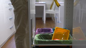 Young Woman Drops The Trash Into Kitchen Recycling Bin. Young Woman Drops The Trash Into Kitchen Recycling Bins stock footage