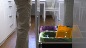 Young Woman Drops The Trash Into Kitchen Recycling Bin. Slow Motion. Young Woman Drops The Trash Into Kitchen Recycling Bins. Slow Motion stock video footage