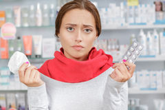 Young woman in drugstore with handkerchief and pills. In drugstore stock image