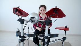 Concept of hobby and music. Young woman drummer practicing electronic drum kit at home. Young woman drummer practicing electronic drum kit at home stock footage
