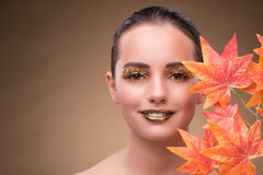 The young woman with dry autumn leaves. Young woman with dry autumn leaves royalty free stock photography