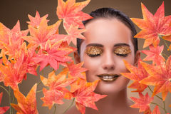 The young woman with dry autumn leaves. Young woman with dry autumn leaves stock image