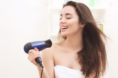 Young woman drying hair after shower. In light bathroom at home Royalty Free Stock Photo
