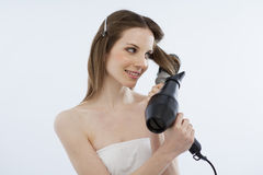 Young woman drying her hair. With hairdryer and hairbrush Royalty Free Stock Photos