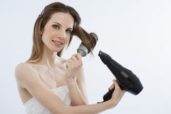 Young woman drying her hair. With hairdryer and hairbrush Stock Photos