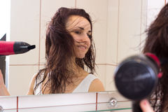 Young woman drying her hair in bathroom Stock Photo
