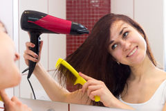 Young woman drying her hair in bathroom Stock Images