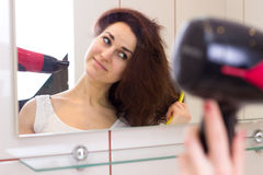 Young woman drying her hair in bathroom Royalty Free Stock Photography