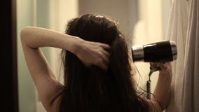 Young woman drying her hair with dryer stock video footage