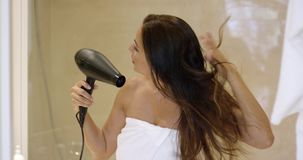 Young woman drying her long dark brown hair stock footage
