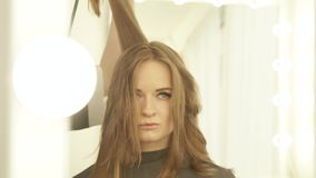 Young woman during drying long hair with dryer and hairbrush front mirror in hairdressing salon. Close up hairstylist stock video footage