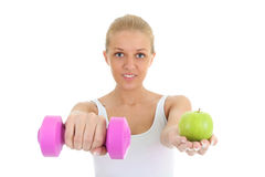 Young woman with dumbbell and apple Stock Images