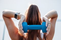 Young woman with dumbbells. back view stock images