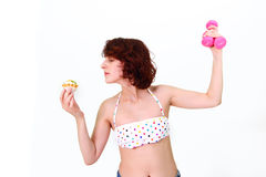 Young woman with dumbbells and cake Stock Image