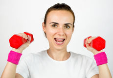 Young woman with dumbbells, isolated Royalty Free Stock Images