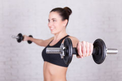 Young woman with dumbbells over white brick wall Royalty Free Stock Photography