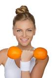 Young woman with dumbbells two ripe oranges Royalty Free Stock Image