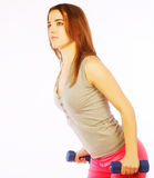 Young woman with dumbbells. Weight isolated over whiter Stock Photography