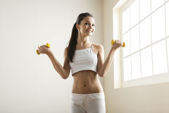 Young woman with dumbells Royalty Free Stock Photos