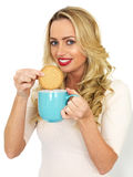 Young Woman Dunking a Biscuit in a Mug of Tea Stock Photos