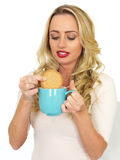 Young Woman Dunking a Biscuit in a Mug of Tea Royalty Free Stock Photography