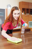 Young woman dusting wooden table Royalty Free Stock Image