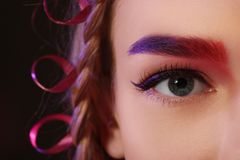 Young woman with dyed eyebrow on dark background,. Closeup stock images