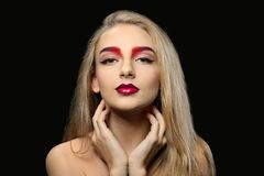 Young woman with dyed eyebrows. On black background stock image